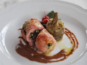Foto pietanza coniglio ripieno di cavolo nero e speck in salsa di prugne